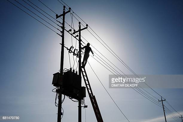An Iraqi minicipal worker fixes the cables of an overhead power line in Mosul's alZahraa neighbourhood on January 11 during an ongoing military...