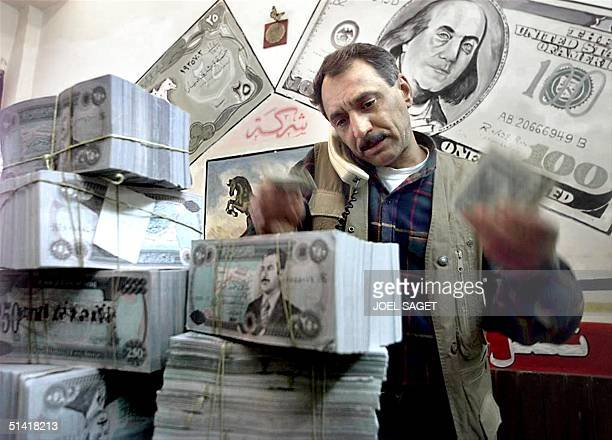 An Iraqi money changer gestures as he talks on the phone, over bundles of Iraqi Dinars under a picture of a one hundred US dollar bill in Baghdad 20...