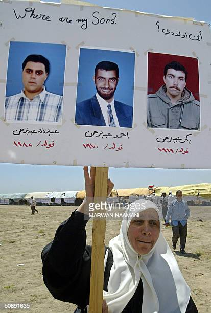 An Iraqi mother holds s placard displaying pictures of her three sons held at the Abu Ghraib prison as she stands at a camp opposite to the detention...