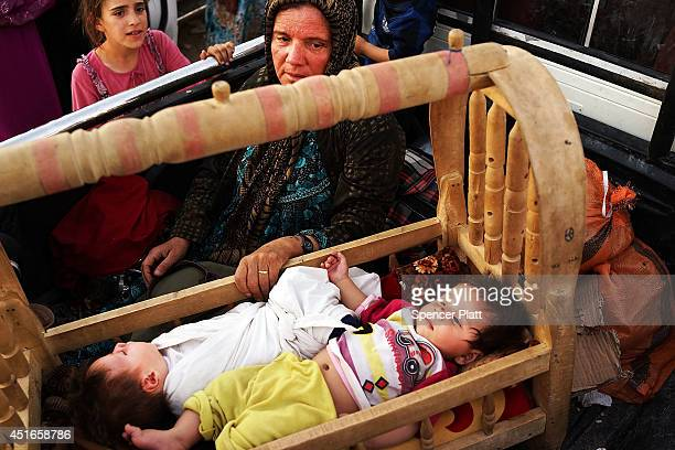 An Iraqi mother who fled recent fighting in the city of Tal Afar rocks her twin children in the back of a pickup truck as they try to enter a...