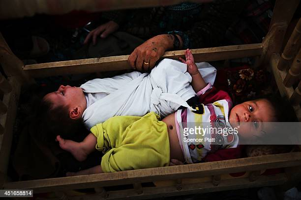 An Iraqi mother who fled recent fighting in the city of Tal Afar rocks her twin sons in the back of a pickup truck as they try to enter a temporary...