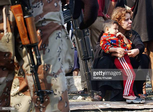 An Iraqi mother with her son look at the area where two suicide car bombs exploded near an Interior Ministry building causing some nearby buildings...