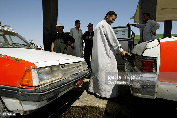 An Iraqi motorist fills his tank at a gas station May 5 2003 in Tikrit Iraq The line for fuel at the station caused by a nationwide gasoline shortage...