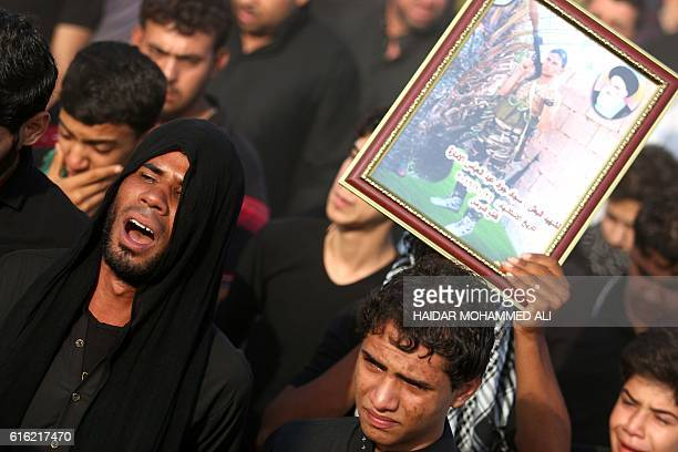 An Iraqi mourner holds a portrait of Jawad alLamara an Iraqi progovernment forces' fighter who was killed in battles against Islamic State group...