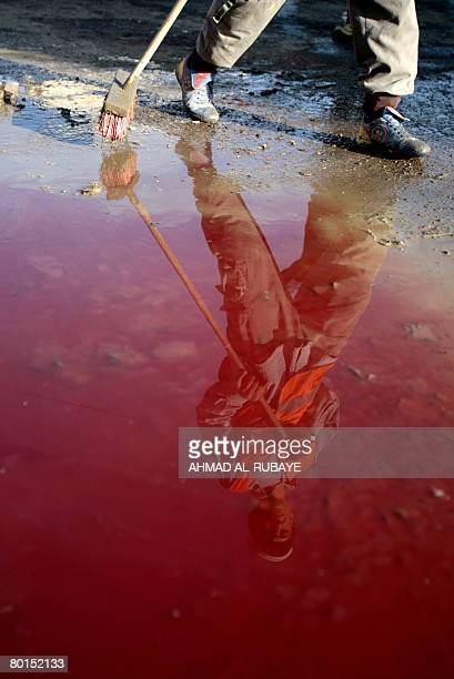 An Iraqi municipality worker is reflected on a pool of blood as he cleans the site of a bomb attack in Baghdad's Karrada neighborhood on March 7 2008...