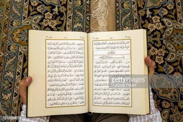 An Iraqi Muslim man reads the Koran on 'Lailat al Qardr' or the 'night of destiny' that during the holy month of Ramadan marks the night when the...