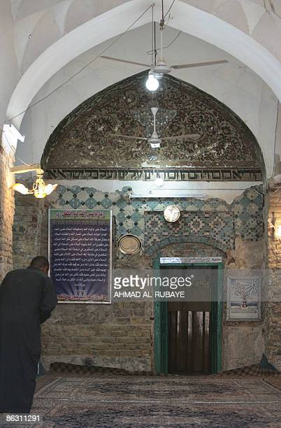 KRAUSS An Iraqi Muslim man stands inside a mosque with Hebrew script inscribed on its entrance arch at the shrine of Ezekiel the Jewish prophet who...