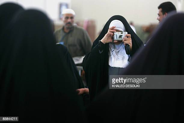 An Iraqi Muslim pilgrim takes a picture of her companions in King Abdul Aziz airport in the Red Sea port city of Jeddah on November 27 2008 Muslim...