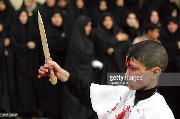 An Iraqi Muslim Shiite boy flagellates himself outside Imam Mussa alKazem shrine in central Baghdad 19 February 2004 at the peak of Ashura which...