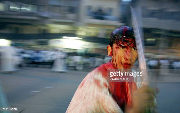 An Iraqi Muslim Shiite flagellates himself outside Imam Mussa alKazem shrine in central Baghdad 19 February 2004 at the peak of Ashura which marks...