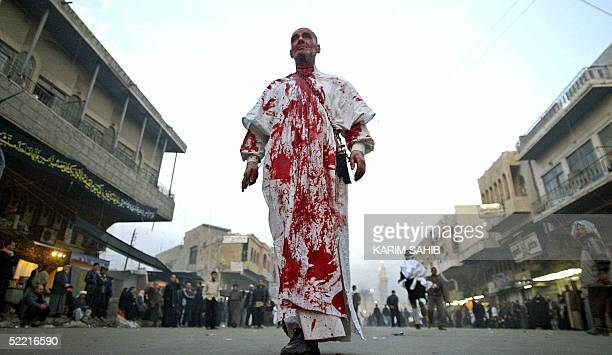 An Iraqi Muslim Shiites walks alone outisde Imam Mussa alKazem in central Baghdad after he flagellated himself 19 February during the peak of Ashura...