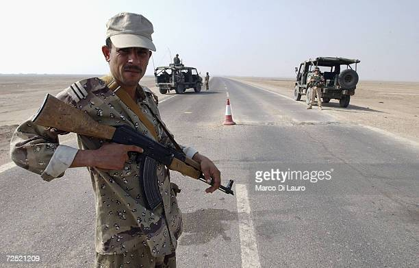 An Iraqi National Guard soldier stands at a check point on the Tampa road from Basrah to Baghdad near the Italian base Camp Mittica on October 11,...