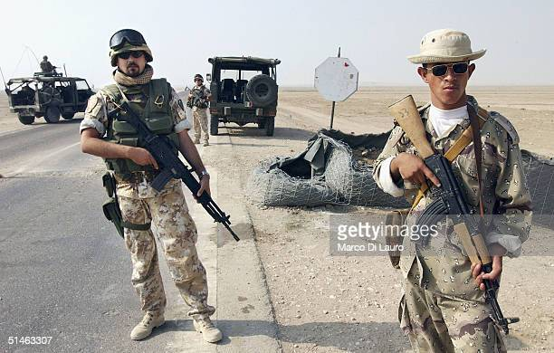 An Iraqi National Guard soldier stands with an Italian Army soldier from the Italian Joint Task Force Iraq, Friuli Brigade, at a check point on the...