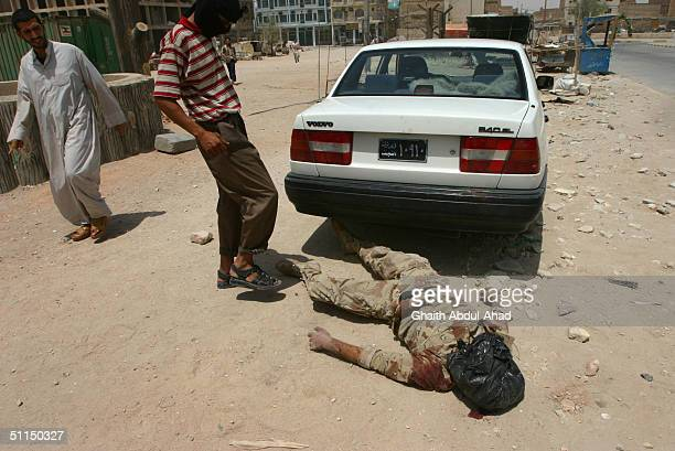 An Iraqi National Guardman lays dead after he was killed during clashes with Iraqi Shiite militiamen August 7 2004 in Najaf Iraq Fighting continued...