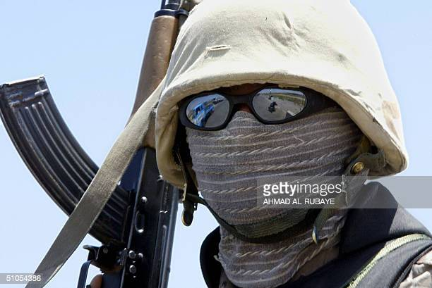 An Iraqi national guardsman stands guard at a checkpoint on the highway joining the flashpoint towns of Ramadi and Fallujah to Baghdad 13 July 2004...