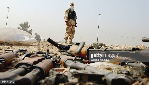 An Iraqi National guardsman stands guard on beside weapons handed over by militiamen loyal to the radical Shiite cleric Moqtada alSadr at a police...