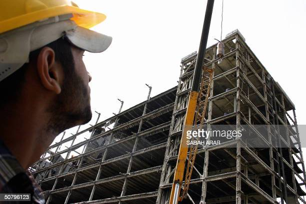 An Iraqi observes the reconstruction of the bombed out Olympic Committee building in Baghdad 03 May 2004. The building hosted the former Iraqi...