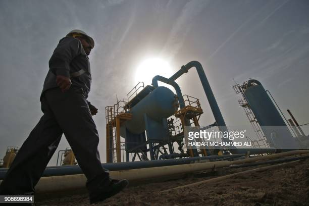 An Iraqi oil technician walks past a gas extraction installation at the Nahr Bin Omar natural gas field north of the southern Iraqi port of Basra on...