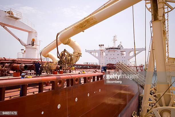 An Iraqi oil worker moves a second loading boom into place on an oil tanker that just arrived to load up with Iraqi crude oil at Al Basra oil...
