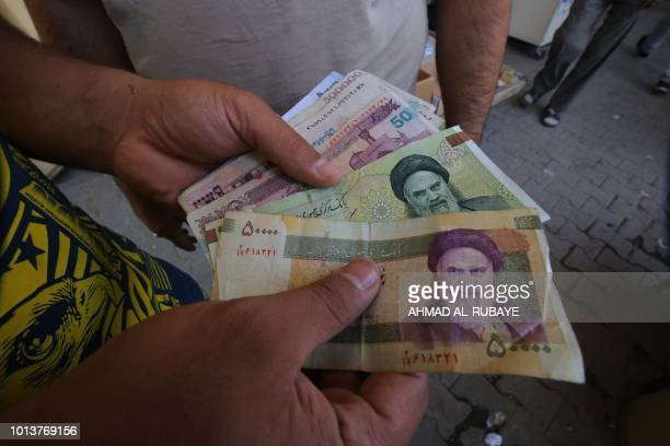 An Iraqi peddler holds in his hand banknotes of Iranian rials for exchange in the Iraqi capital Baghdad on August 9 2018 Caught in the crossfire...
