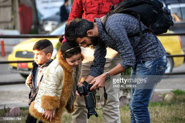 An Iraqi photographer shows a girl a picture taken on his camera at Nafoura square in the alZuhur neighborhood in the eastern part of the northern...
