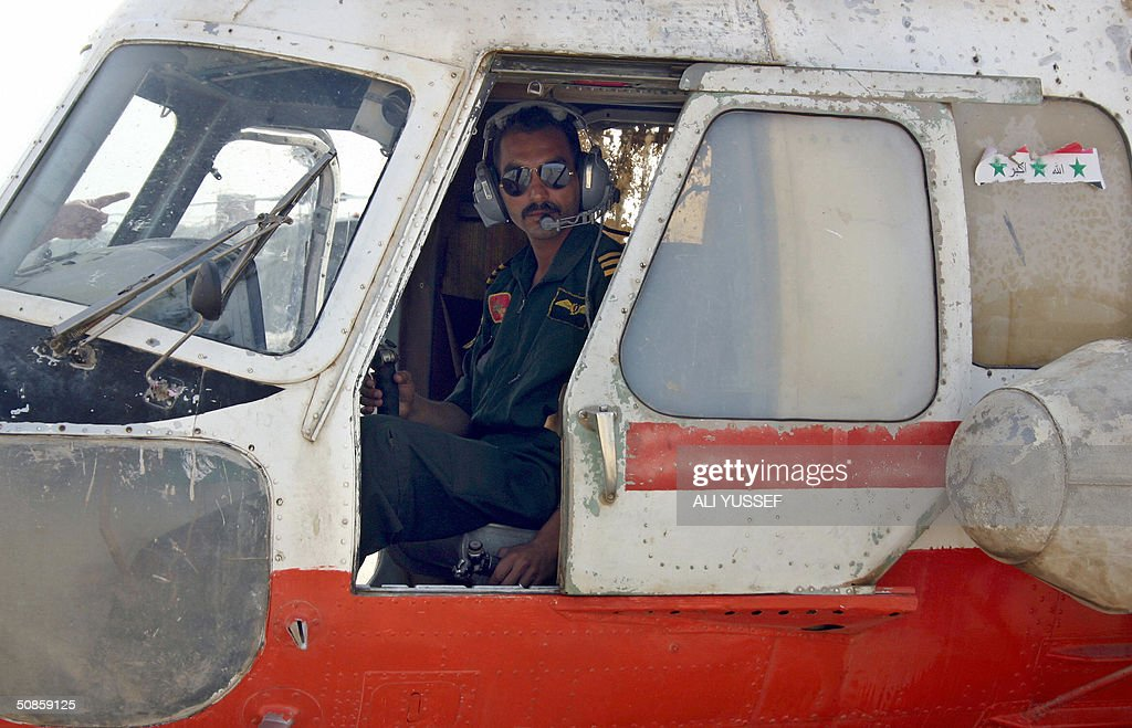 An Iraqi pilots sits inside his Russian-made MI-2 Iraqi helicopter before taking off to begin crop-dusting the date palm fields in the city of Baquba, northeast of Baghdad 20 May 2004. Iraqi pilots are flying again for the first time since the war started over a year ago, to spray date palm fields in a joint operation with coalition forces in eastern Iraq.