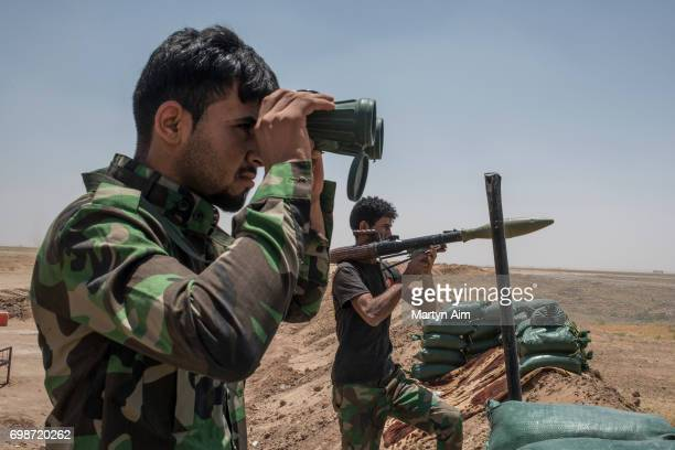 An Iraqi PMF fighter looks through binoculars June 20 2017 on the IraqSyria border in Nineveh Iraq The Popular Mobilisation Front forces composed of...