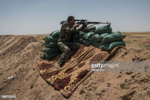 An Iraqi PMF fighter looks through the sight of a sniper rifle June 20 2017 on the IraqSyria border in Nineveh Iraq The Popular Mobilisation Front...