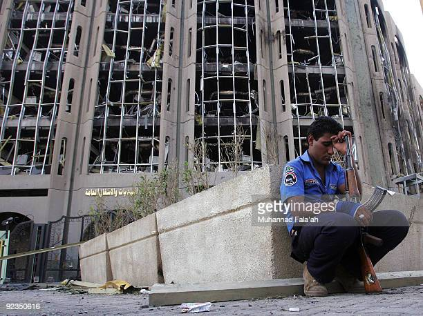 An Iraqi police man crouches at the site of yesterday's car bomb explosion the Ministry of Justice on October 26 2009 in Baghdad Iraq Two car bombs...
