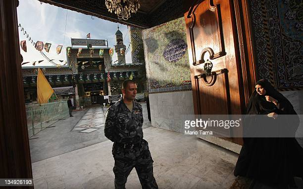 An Iraqi Police officer and woman walk at the entrance to the Seid Idrees mosque during preparation for the festival Ashura on December 5 2011 in...