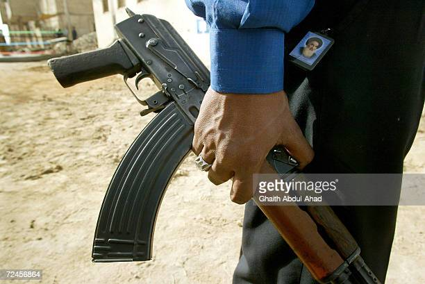 An Iraqi police officer carrying a gun and a picture of Grand Ayatollah Ali Sistani stands guard at a polling station, January 29, 2005 in the Shiite...