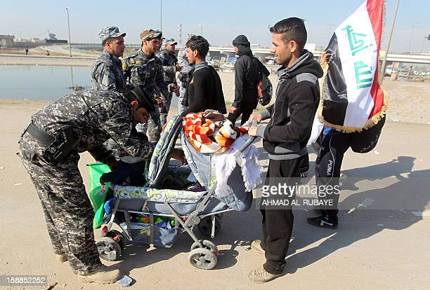 An Iraqi police officer searches a pram as Shiite Muslim pilgrims march along the main highway that links the Iraqi capital Baghdad with the central...