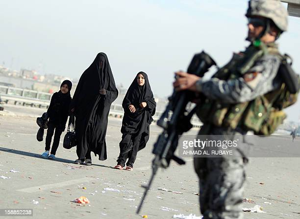 An Iraqi police officer stands guard as Shiite Muslim pilgrims march along the main highway that links the Iraqi capital Baghdad with the central...