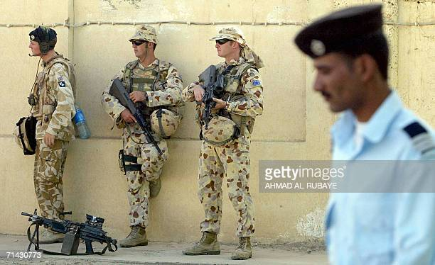 An Iraqi police officer walks past Australian soldiers during a handover ceremony in the southern city of Samawa 13 July 2006 Iraqis took charge...