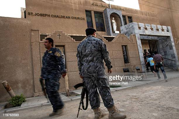 An Iraqi police officers stands guard outside of St Joseph Chaldean Church following a Sunday service on July 24 2011 in Baghdad Iraq Forming one of...