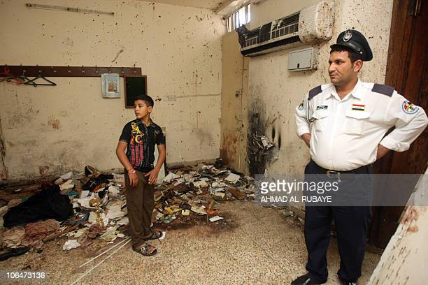 An Iraqi policeman and a boy stand at the priest's room in the Sayidat alNejat Catholic Cathedral or Syrian Catholic Church in central Baghdad on...