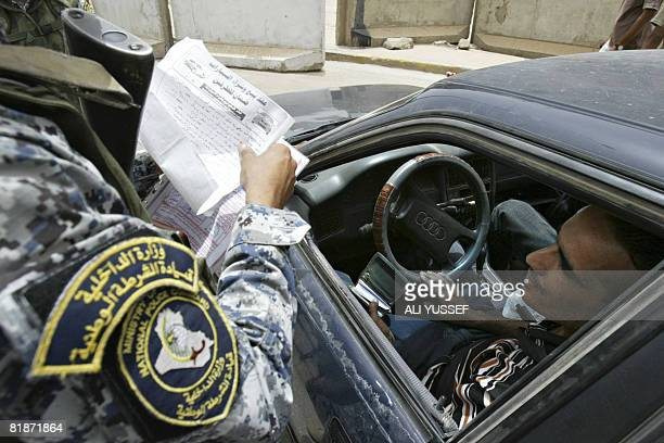 An Iraqi policeman checks the registration papers of a vehicle at a checkpoint on Palestine street in Baghdad on July 9 2008 At least 13 people were...