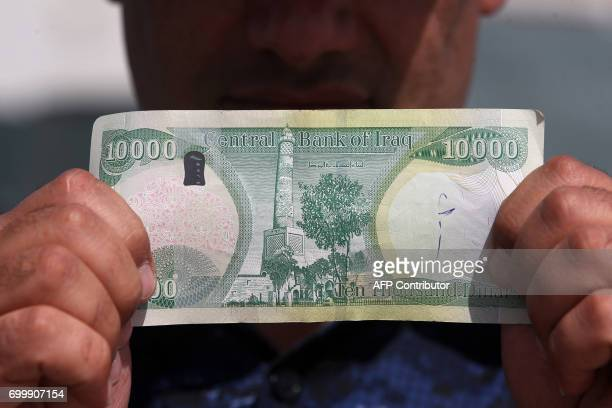 An Iraqi policeman displays a 10000Iraqi dinar banknote bearing an image of Mosul's iconic leaning minaret known as the 'Hadba' on June 22 in Mosul /...