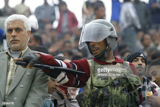 An Iraqi policeman in riot gear gestures as he guards the crowd during the final between rival Baghdad clubs alZawra and alTalaba of the Baghdad Cup...