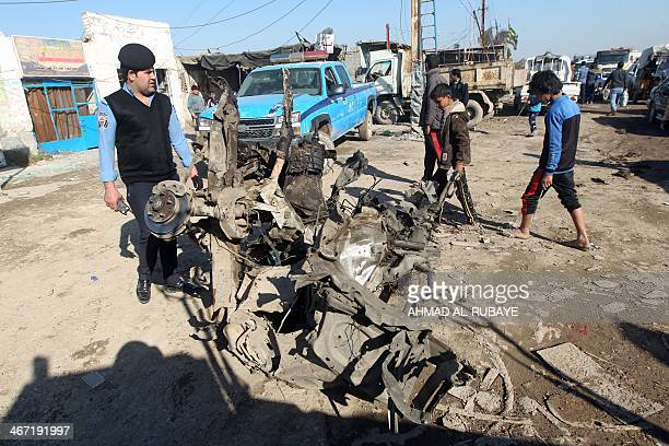 An Iraqi policeman inspects a burnt out vehicle at the site of car bomb explosions on February 6 2014 in alObeidi Shiite neighbourhood on the eastern...
