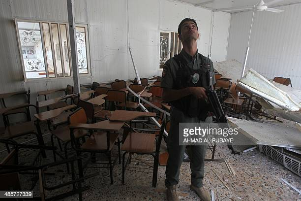 An Iraqi policeman inspects a classroom following a suicide bombing at the university of Imam Kadhim University in the capital Baghdad on April 20...