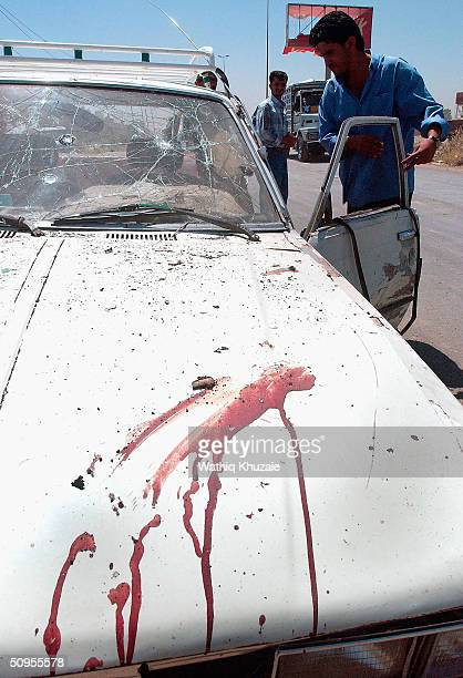An Iraqi policeman investigates the scene of a car bomb attack in which at least 12 people were killed, among them 4 Iraqi policemen, on June 13,...