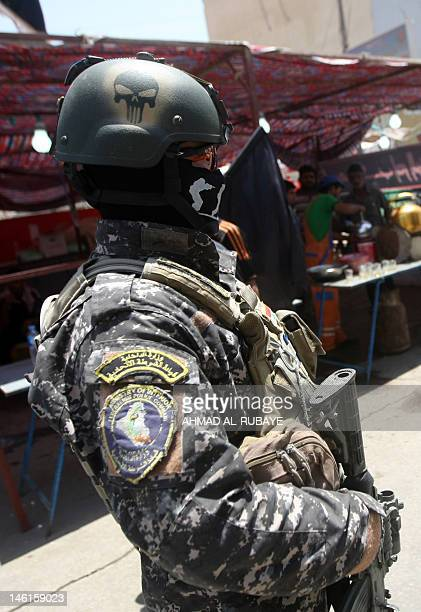 An Iraqi policeman keeps guard as Shiite Muslim women walk to the Kadhimiyah area of north Baghdad to mark the anniversary of the death of Imam Musa...