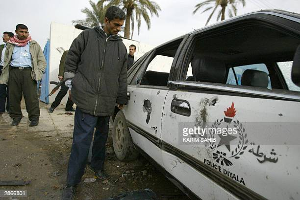 An Iraqi policeman looks at a destroyed police car after a suicide car bomber blew himself up outside a police station in Baquba 50km northeast of...