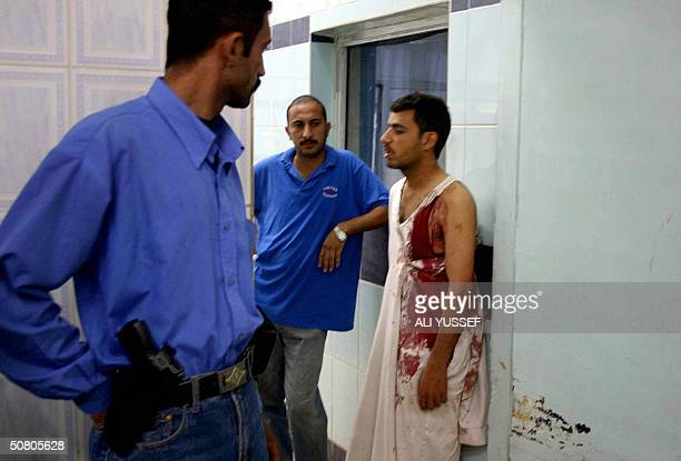 An Iraqi policeman looks at a wounded civilian in a local hospital in the city of Baquba northeast of Baghdad 06 May 2004 Four civilians were wounded...