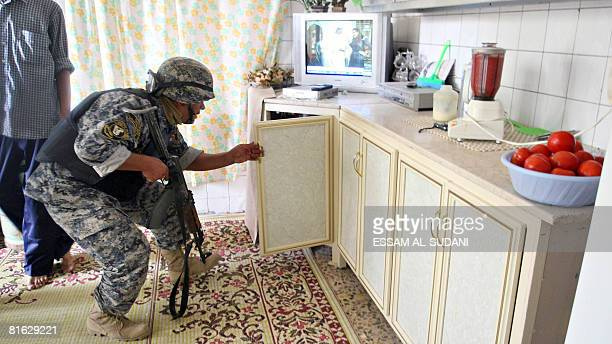 An Iraqi policeman looks inside a kitchen cupboard in a residence during a housetohouse search for weapons and militants in the southern city of...