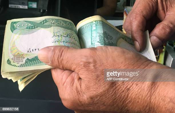 An Iraqi policeman pays for groceries with 10000Iraqi dinar banknotes bearing an image of Mosul's iconic leaning minaret known as the 'Hadba' on June...