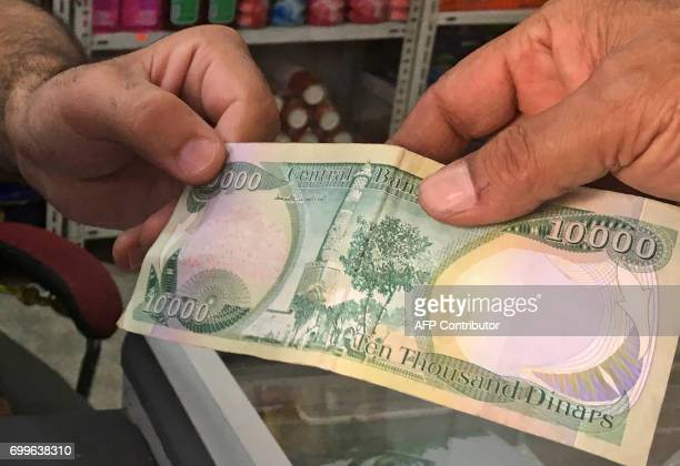 An Iraqi policeman pays for groceries with a 10000Iraqi dinar banknote bearing an image of Mosul's iconic leaning minaret known as the 'Hadba' on...