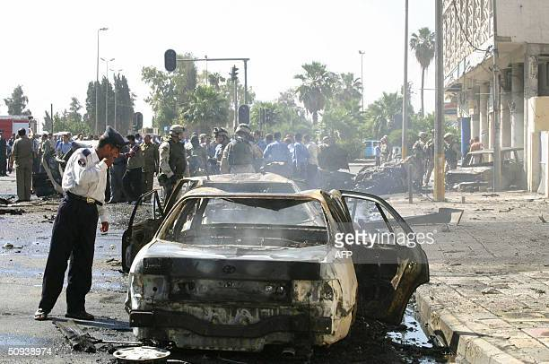 An Iraqi policeman peers into a smoldering vehicle following a car bomb and a roadside bomb in the northern city of Mosul some 370 kms from Baghdad...