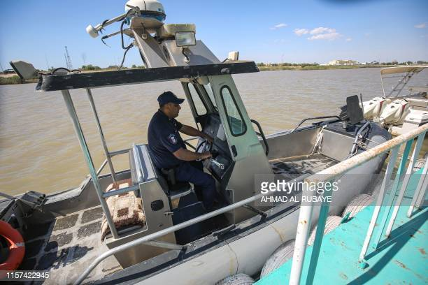 An Iraqi policeman pilots a speedboat while on patrol to prevent people attempting suicide from jumping in the Tigris river in the centre of the...